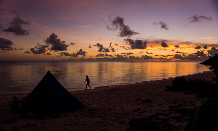 A kayaker stretches her legs, walking along the beach after a long day cooped up in a boat